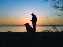 Siluetta dell'uomo e del cane sopra il tramonto Fotografie Stock Libere da Diritti