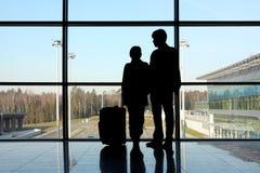 Siluetta dell'uomo e della ragazza che si levano in piedi finestra vicina Immagini Stock