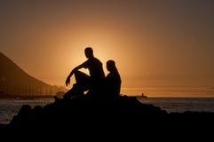 Siluetta dell'uomo e delle donne contro il tramonto fotografia stock
