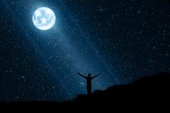 Siluetta dell'uomo felice che gode della notte con la luna e le stelle Fotografie Stock