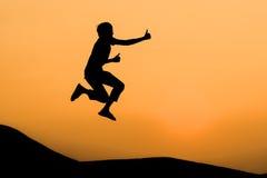 Siluetta dell'uomo nel salto e nel colpo felici su sul tramonto arancio Immagine Stock