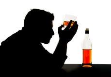 Siluetta dell'uomo potabile alcoolizzato con il vetro del whiskey nella siluetta di dipendenza di alcool fotografia stock