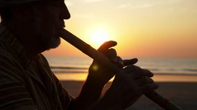 Siluetta dell'uomo senior che gioca flauto di bambù sulla spiaggia al tramonto archivi video