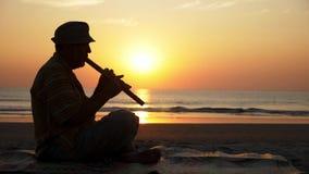 Siluetta dell'uomo senior che gioca flauto di bambù sulla spiaggia al tramonto video d archivio