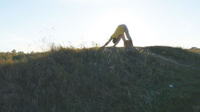 Siluetta dell'uomo sportivo che sta alla posa di yoga all'aperto Gli Yogi che praticano l'yoga si muovono e posizionano in natura Fotografie Stock