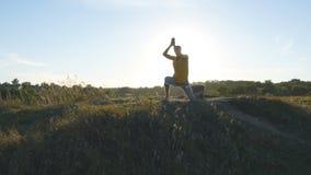 Siluetta dell'uomo sportivo che sta alla posa di yoga all'aperto Gli Yogi che praticano l'yoga si muovono e posizionano in natura Immagine Stock Libera da Diritti