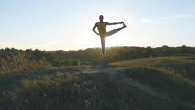 Siluetta dell'uomo sportivo che sta alla posa di yoga all'aperto Gli Yogi che praticano l'yoga si muovono e posizionano in natura Fotografia Stock