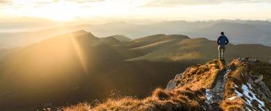 Siluetta dell'uomo sulla cima il picco della montagna su alba fotografie stock