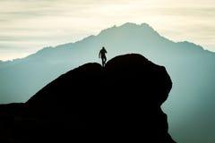 Siluetta dell'uomo sulla roccia in montagne Fotografie Stock