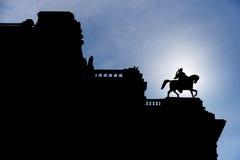 Siluetta dell'uomo sulla statua del cavallo sopra l'edificio di Vienna Fotografia Stock Libera da Diritti