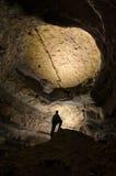 Siluetta dell'uomo in una caverna enorme di buio Immagine Stock