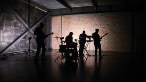 Siluetta della banda rock di concerto che esegue in scena con l'esecutore del cantante, chitarra, batterista, video musicale del  stock footage