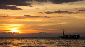 Siluetta della barca che attraversa l'oceano verso un cielo arancio di tramonto sull'orizzonte Immagine Stock Libera da Diritti