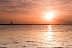 Siluetta della barca di navigazione sopra il tramonto Fotografia Stock