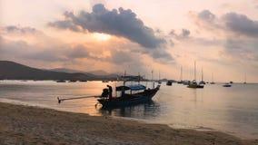 Siluetta della barca di Thai Wooden Sail Longtail del pescatore che galleggia sul mare Colori stupefacenti del tramonto tropicale video d archivio