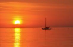Siluetta della barca a vela all'insieme del sole Immagini Stock Libere da Diritti