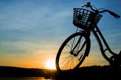 Siluetta della bicicletta su un fondo del tramonto Fotografia Stock