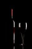 Siluetta della bottiglia e del vetro del vino rosso su fondo nero Fotografia Stock