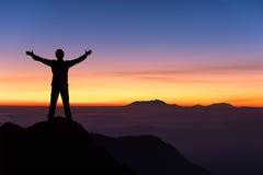 Siluetta della condizione dell'uomo e della mano spanta sulla cima del mountai Immagine Stock Libera da Diritti