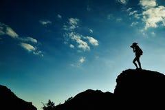 Siluetta della donna al tramonto in montagne Immagini Stock Libere da Diritti