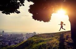 Siluetta della donna alla vista della città di tramonto Fotografia Stock