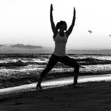 Siluetta della donna in buona salute in abiti sportivi sull'allenamento del litorale Immagine Stock Libera da Diritti