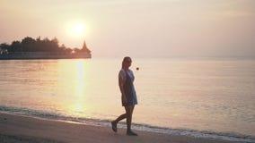 Siluetta della donna che cammina alla spiaggia durante il bello tramonto Concetto di vacanza e di viaggio stock footage