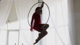 Siluetta della donna che fa alcuni elementi acrobatici sul cerchio aereo stock footage