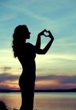 Siluetta della donna che fa il segno del cuore Immagini Stock