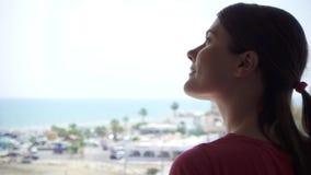 Siluetta della donna che gode della vista del mare dal terrazzo Viaggiatore femminile che esamina porticciolo dal balcone archivi video