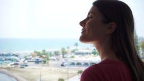 Siluetta della donna che gode della vista del mare dal terrazzo Viaggiatore femminile che esamina porticciolo dal balcone video d archivio