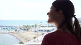 Siluetta della donna che gode della vista del mare dal terrazzo Viaggiatore femminile che esamina porticciolo dal balcone stock footage