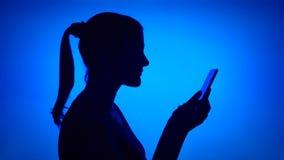 Siluetta della donna che per mezzo del cellulare su fondo blu Fronte femminile del ` s nel profilo che passa in rassegna, chiacch stock footage