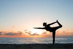 Siluetta della donna che pratica yoga autentica sulla spiaggia al tramonto fotografie stock