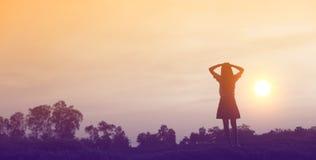 Siluetta della donna che prega su bello fondo del cielo Fotografie Stock Libere da Diritti