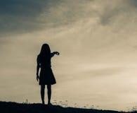 Siluetta della donna che prega su bello fondo del cielo Immagine Stock Libera da Diritti