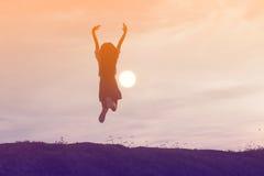 Siluetta della donna che prega su bello fondo del cielo Immagini Stock