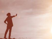 Siluetta della donna che prega su bello fondo del cielo Immagini Stock Libere da Diritti