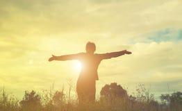 Siluetta della donna che prega su bello fondo del cielo Fotografia Stock Libera da Diritti