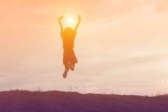 Siluetta della donna che salta contro il bello cielo Immagine Stock