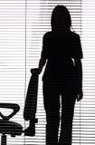 Siluetta della donna che si leva in piedi vicino alla presidenza (ciechi) fotografia stock