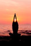 Siluetta della donna che si siede nella posa di yoga sul fondo del mare indietro acceso Immagine Stock