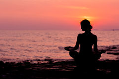 Siluetta della donna che si siede nella posizione di loto sul fondo del mare indietro acceso Immagini Stock