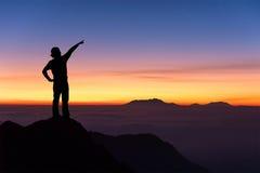 Siluetta della donna che sta sulla cima della montagna e di indicare Fotografie Stock