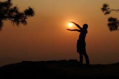 Siluetta della donna che tiene il sole Immagine Stock
