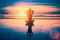 Siluetta della donna di yoga di meditazione sulla spiaggia dell'oceano Fotografia Stock
