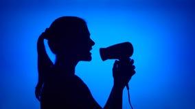 Siluetta della donna divertendosi canto nel fon Dancing femminile sciocco su fondo blu video d archivio