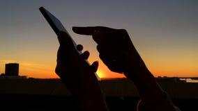Siluetta della donna facendo uso dello smartphone in citt? al tramonto archivi video