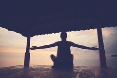 Siluetta della donna felice che fa pratica di forma fisica nel riparo del sole vicino all'oceano fotografia stock