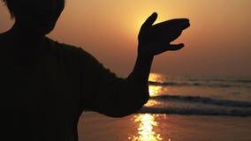 Siluetta della donna senior attiva che pratica 'chi' del tai relativo alla ginnastica sulla spiaggia sabbiosa video d archivio